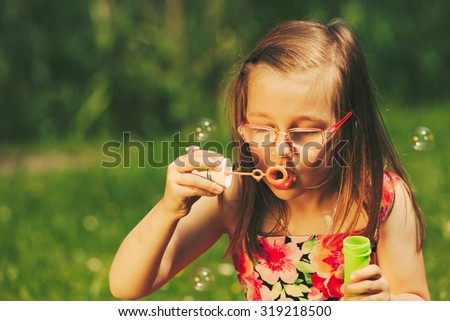 Little girl child blowing soap bubbles outdoor. Kid having fun in park. Happy and carefree childhood. Instagram filtered.