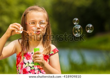 Little girl child blowing soap bubbles outdoor. Kid having fun in park. Happy and carefree childhood.