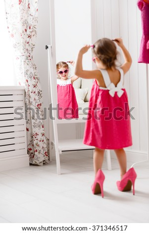 child looking in mirror. little girl child fashionista looking in the mirror at home a pink dress shoes