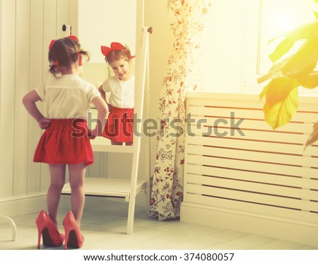 little girl child fashionista looking in the mirror at home in a red skirt, shoes of mother