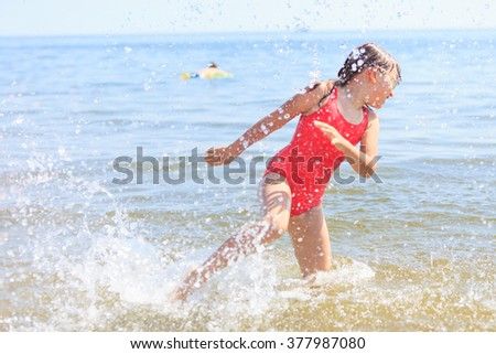 Little girl child having fun in ocean. Kid and woman bathing splashing sea water. Summer vacation holiday relax. - stock photo