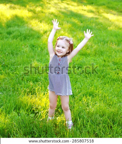 Little girl child having fun on the grass in sunny summer day - stock photo