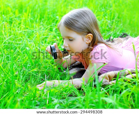 Little girl child looking through a magnifying glass on the grass - stock photo