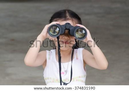 Little girl child looks in binoculars - stock photo