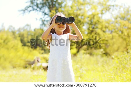 Little girl child looks in binoculars outdoors in summer day - stock photo