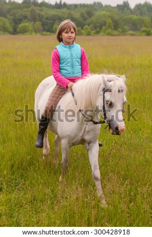 Little girl child walks on a white horse on the field