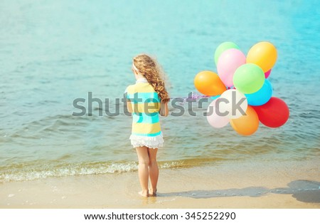 Little girl child with balloons standing on beach near sea, view back - stock photo