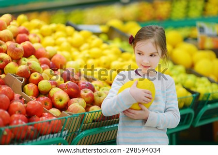 Little girl choosing a melon in a food store or a supermarket - stock photo