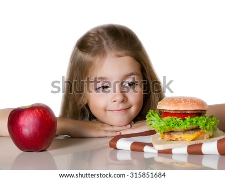Little girl choosing between healthy and harmful food.Kid hesitating between apple and hamburger.Isolated.Unhealthy nutrition. - stock photo