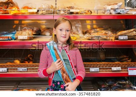 Little girl choosing bread in a food store - stock photo