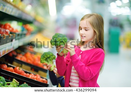 Little girl choosing fresh broccoli in a food store or a supermarket - stock photo