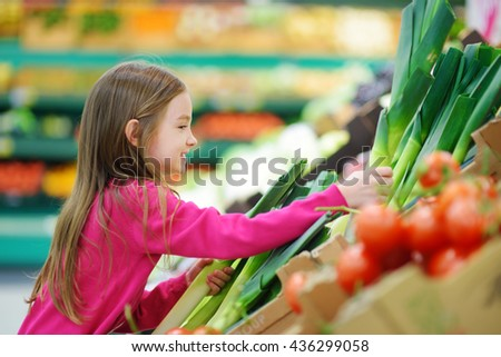 Little girl choosing fresh leek in a food store or supermarket - stock photo