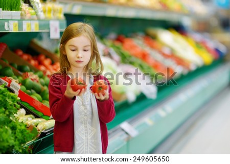 Little girl choosing tomatoes in a food store - stock photo