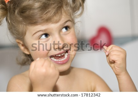 Little girl cleaning teeth by floss in bath - stock photo
