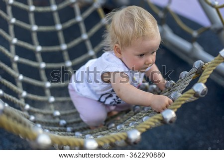 little girl climbing net at playground