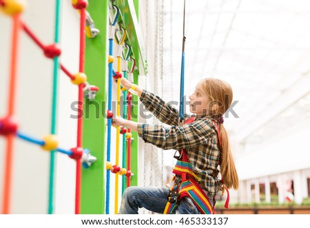 little girl climbing the wall on safety ropes in entertainment center