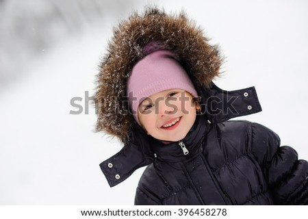 Little girl close-up portrait smiling and walking in the winter outdoors. Children outdoor. Happy kid, child having fun in beautiful winter park during snowfall. - stock photo