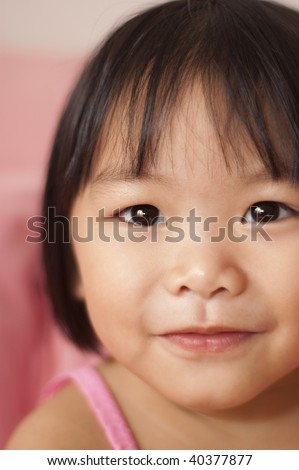 Little girl. Close-up shot of a young Asian girl with smile on her face. - stock photo