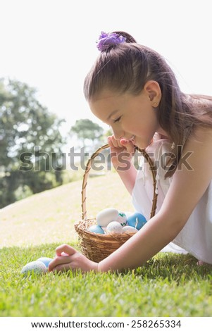 Little girl collecting easter eggs outside in the garden - stock photo