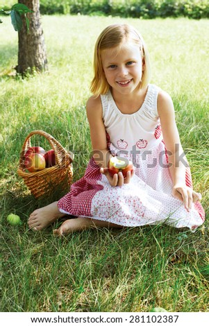 Little girl collects the apples in the apple orchard