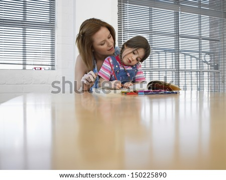 Little girl coloring book while mother assisting her at table in house - stock photo