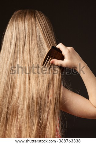 Little girl combing her beautiful long hair, black background - stock photo