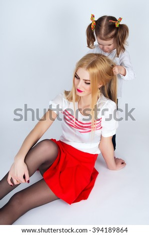 Little girl combing her hair a beautiful mother in the background