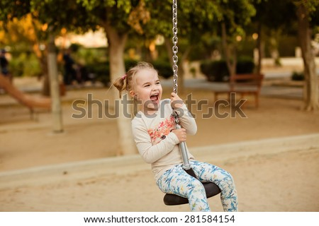Little girl contagious laugh, riding on a bungee swing on the background of the Park in the summer - stock photo