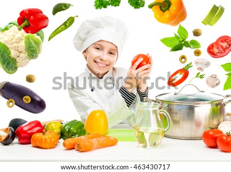 little girl-cook by table with flying vegetables in white uniform