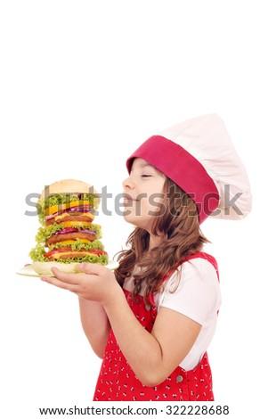 little girl cook enjoys a large hamburger  - stock photo