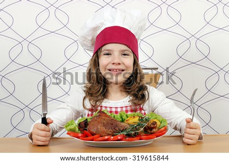 little girl cook with big turkey drumstick on table - stock photo