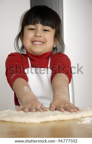 Little girl cooking a pizza in a kitchen.Little kid in a kitchen. - stock photo