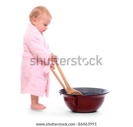 LIttle girl cooking i the big pot. - stock photo