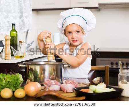 Little girl cooking soup in pan - stock photo