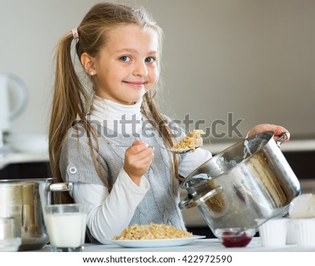 Little girl cooking tasty and healthy porridge in kitchen - stock photo