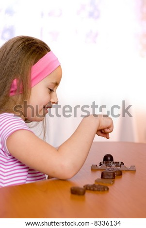 Little girl counting assorted chocolates on table - stock photo