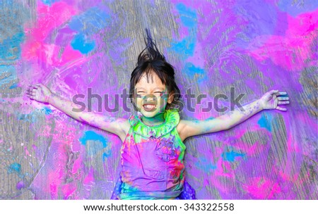 little girl covered in colorful paint - stock photo