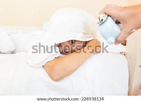 Little girl covering head with pillow and being awakened by alarm clock - stock photo