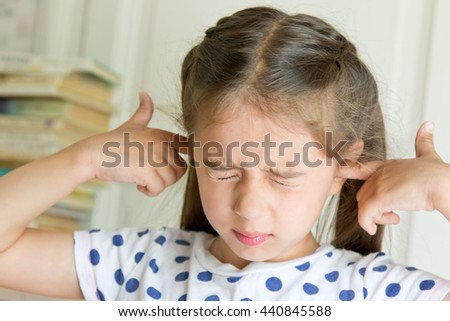 Little girl covering her ears. Negative emotion  - stock photo
