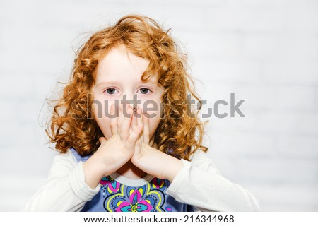 Little girl covering her mouth with her hands. Surprised or scared. On the light background indoors. - stock photo