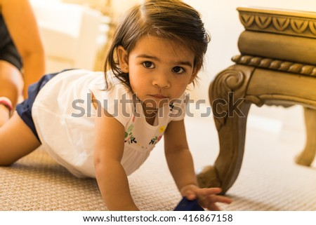 Little girl crawling around on the floor inside a home. - stock photo