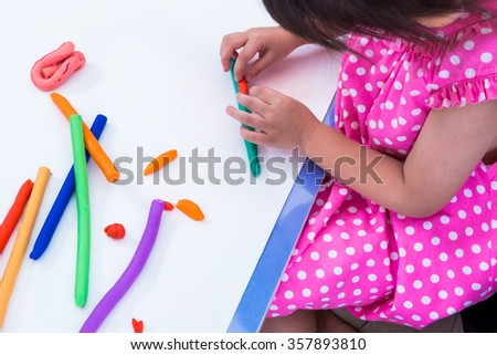 Little girl creating toys from play dough. Child moulding modeling clay. Strengthen the imagination of child - stock photo