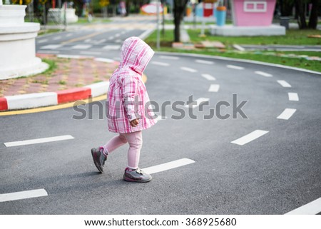 Little girl crossing the road on the crosswalk in the park