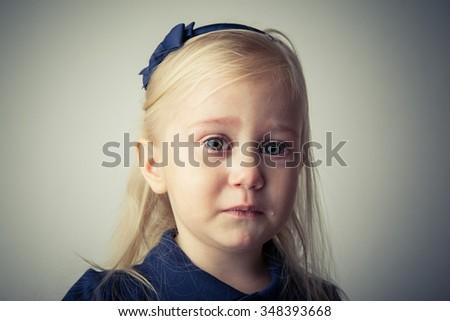 Little girl crying. Really upset. Tears on her cheek. - stock photo