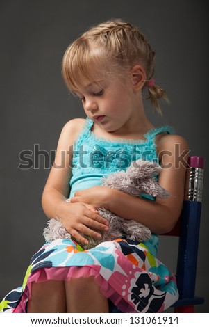 Little girl cuddling her favourite soft toy - stock photo
