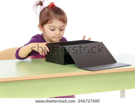 Little girl curiously looking at the big black box.concept childhood education and child development.Isolated on white background - stock photo
