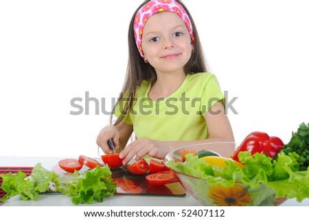 little girl cut fresh vegetables. Isolated on white background - stock photo
