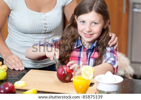 Little girl cuts apple - stock photo