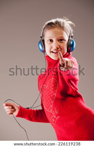 Little girl dancing and pointing her finger to you while listening to the music in her blue headphones and dancing - stock photo