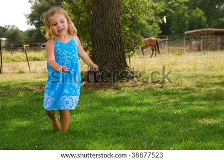 Little girl dancing in the grass at a horse farm - stock photo